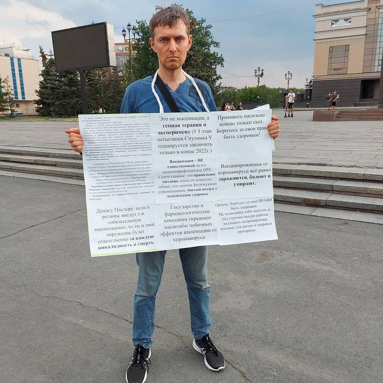 Вильгельм Варкентин на пикете держит плакат с призывов к людям сохранять свое здоровье и не соглашаться на жижизацию