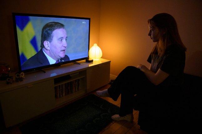 Телевизор с теле видением в помещении камерного типа: и женщина смотрит